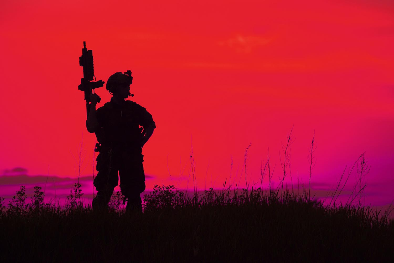 Silueta de soldado u oficial militar con armas al atardecer